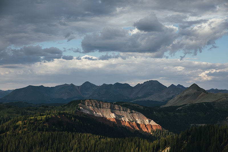 A wide view of Colorado's peaks, with a striped colors of red and grey rocks.