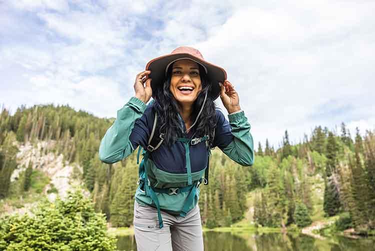 A woman smiles whil wearing a sun hat next to a mountain lake.