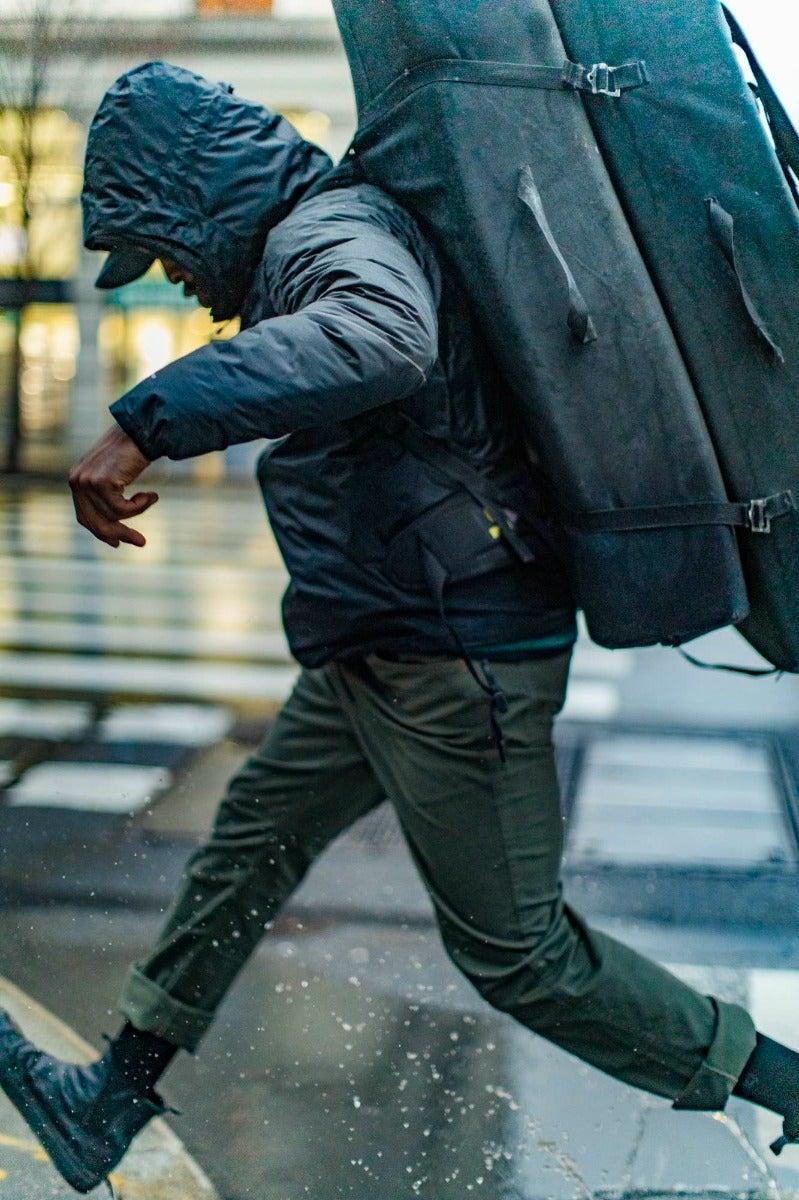A traveler enjoys splashing in a puddle on a rainy city day.