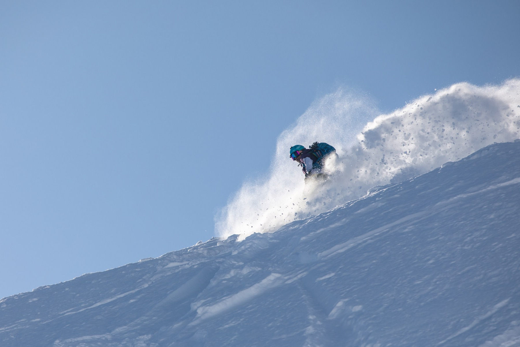 Dani Reyes-Acosta carves a steep powder turn on her snowboard with a blue sky background.
