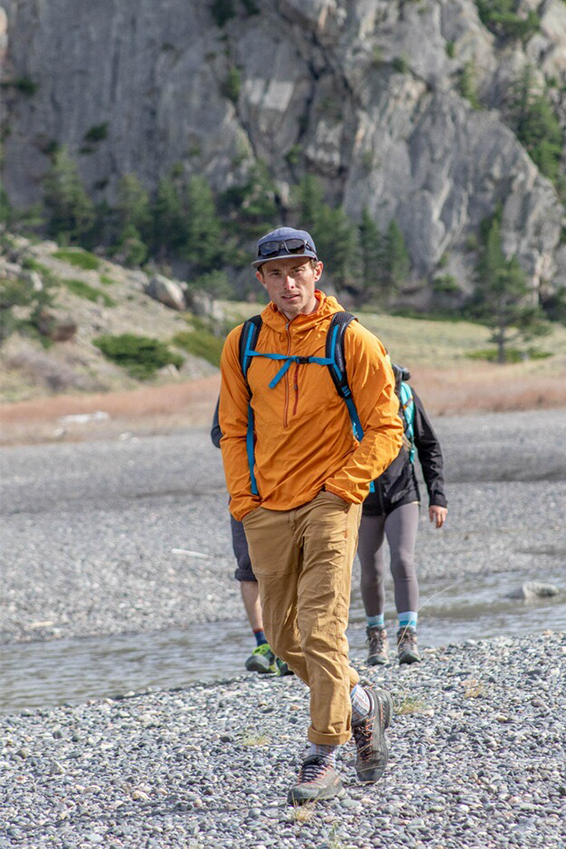 Justin Willis hikes through a riverbed wearing an Outdoor Research Sun Hoodie