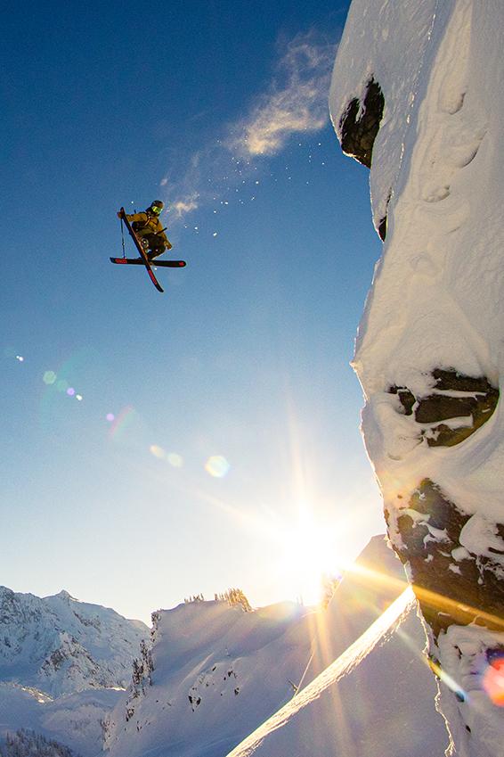 Micah Evangelista catching huge air with skis crossed in an X