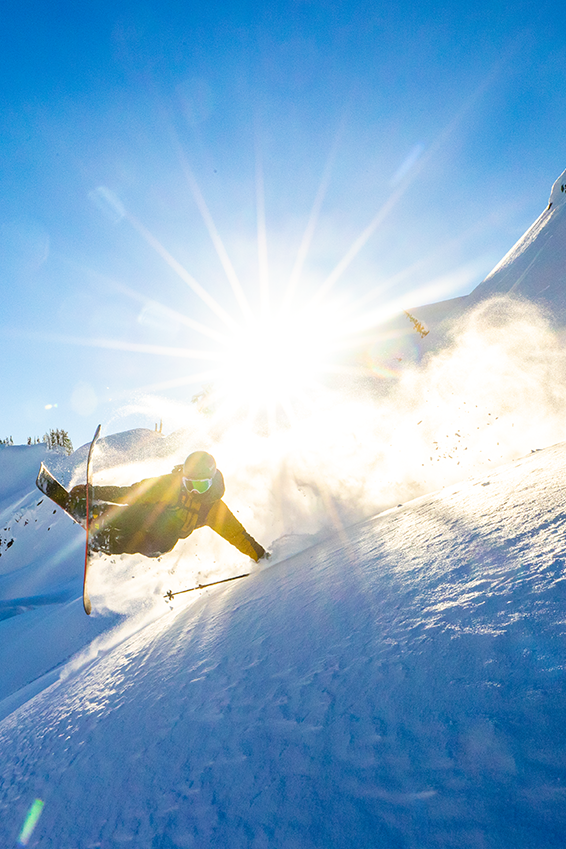 Micah Evangelista skiing with the sun shining behind him