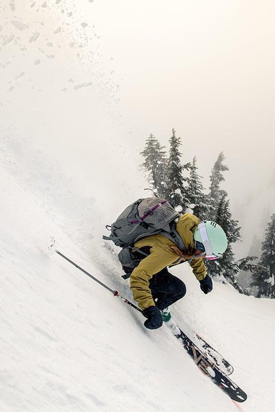 Jess Baker descending a steep ski line on a foggy day