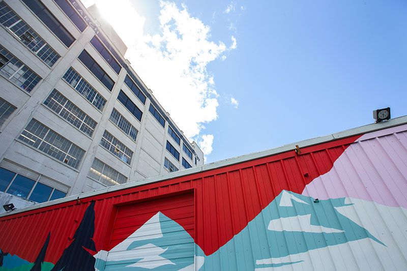 Looking up at the Outdoor Research Seattle Headquarters building, with a colorful mural in the foreground and blue skies above.