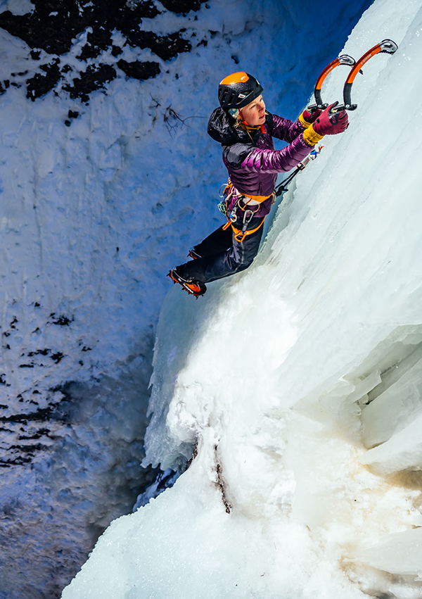 Emilie Drinkwater ice climbing in the Helium Down Hoodie and Archangel bibs