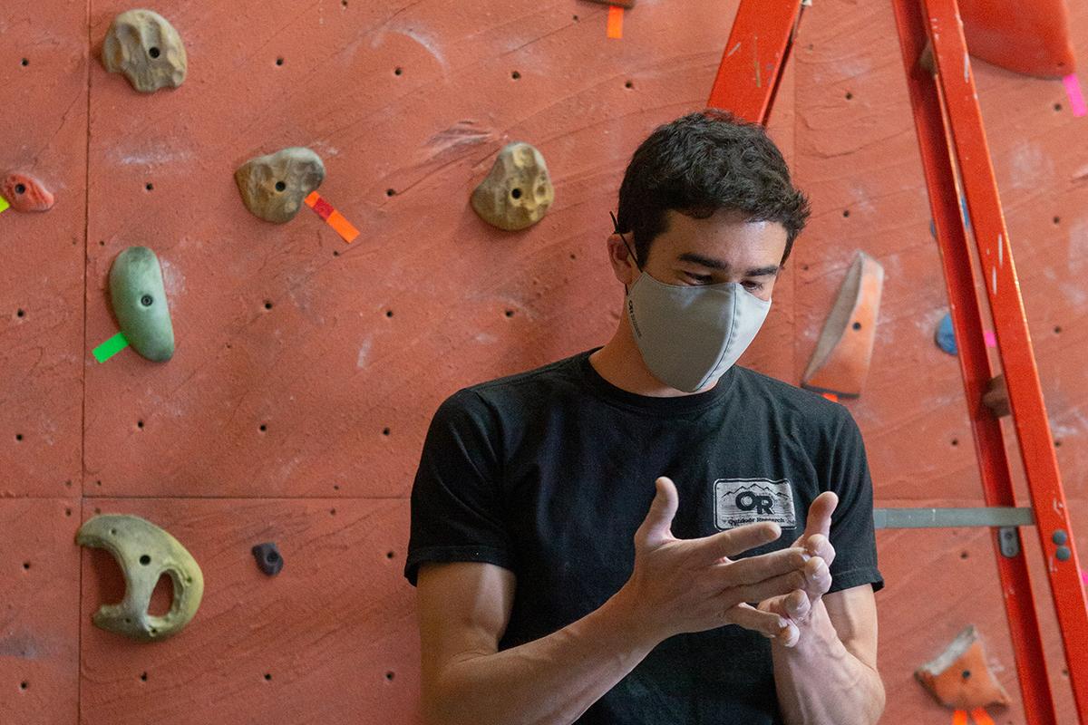 Outdoor Research Climbing Ambassador, Keenan Takahashi smiling under and OR Face Mask, at an indoor climbing gym